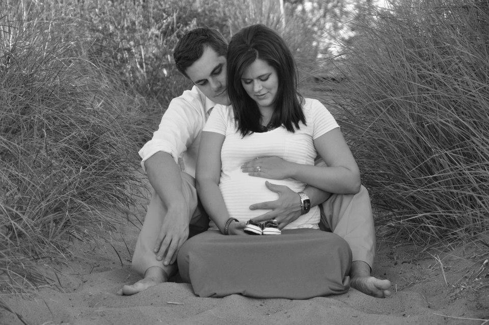 man and woman holding pregnant belly
